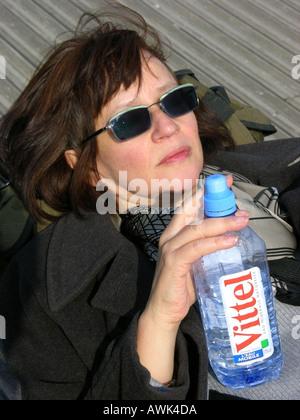 France Ile de France Paris Pont de Solferino woman sunbathing on bench and holding bottle of mineral water Vittel - Stock Photo
