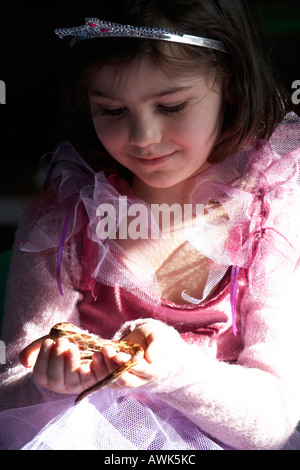 Young girl in princess costume holding a snake reptile at a children s educational birthday party in John Grooms - Stock Photo
