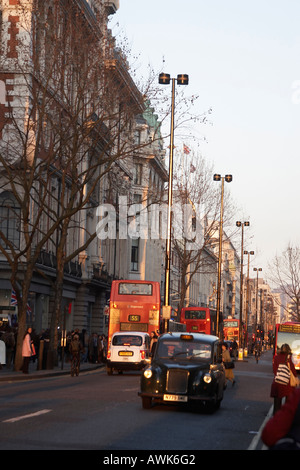 Red London Buses taxis and winter shoppers in evening sunlight on Oxford Street London W1 England - Stock Photo