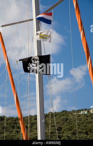 scull and crossbones at a mast in the harbour - Stock Photo