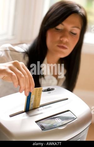 woman shredding credit card - Stock Photo