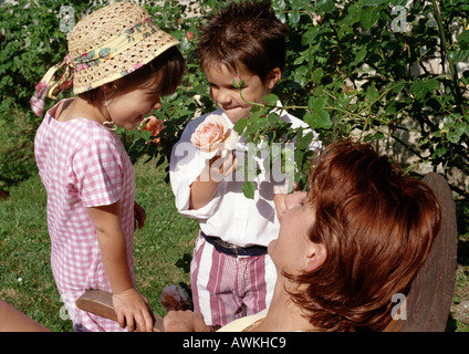 Young boy holding rose for young girl to smell in garden, mother watching. - Stock Photo