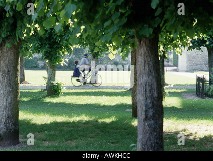 People riding through park on bicycle - Stock Photo