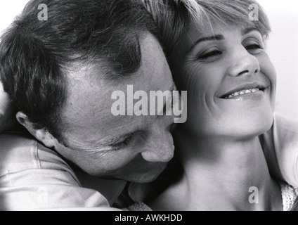 Man hugging woman from behind, close up, black and white. - Stock Photo