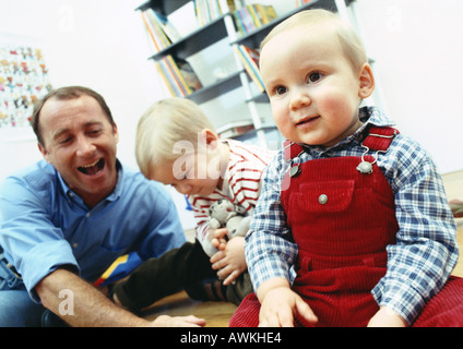 Father sitting on floor with young sons inside. - Stock Photo