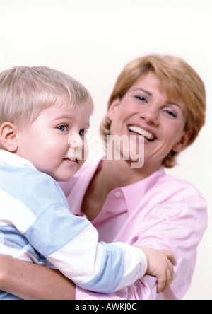 Woman smiling, holding young boy in hands. - Stock Photo