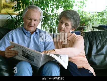 Senior couple on couch reading newspaper. - Stock Photo
