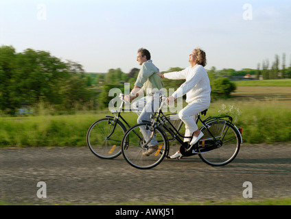 Couple riding bicycles together in countryside - Stock Photo