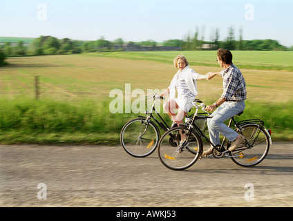 Man and woman riding bicycles,  holding hands, countryside in background - Stock Photo