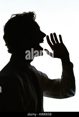 Man yelling with hand out in front of mouth, silhouette - Stock Photo
