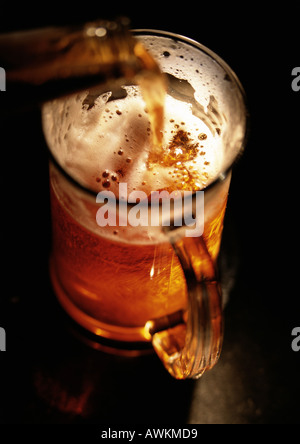 Beer being poured into mug, high angle view, close-up - Stock Photo