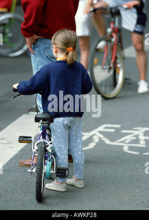 Little girl standing beside bicycle in bikelane, rear view - Stock Photo