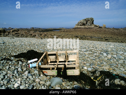 Trash scattered on rocky beach - Stock Photo