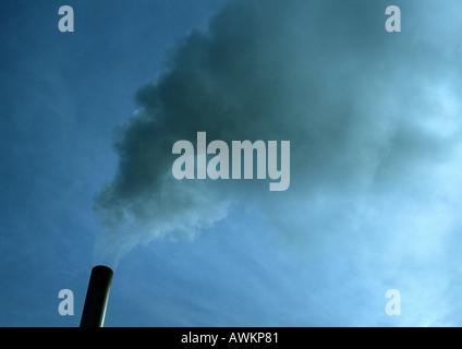 Smoke stack spewing smoke, low angle view - Stock Photo