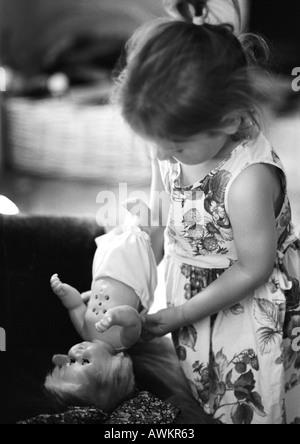 Girl holding baby doll, b&w - Stock Photo