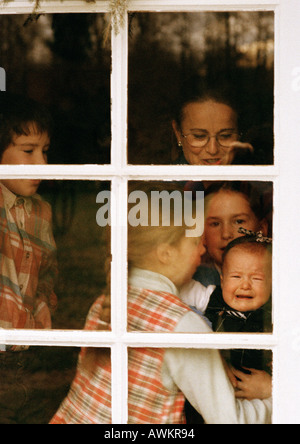Mature woman and children behind window - Stock Photo