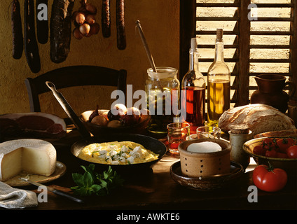 Table spread with various foods and cooking ingredients - Stock Photo
