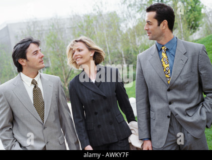 Three business people walking outside,smiling - Stock Photo