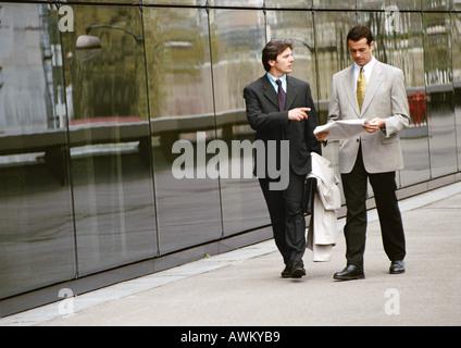 Two businessmen walking along sidewalk in front of building - Stock Photo