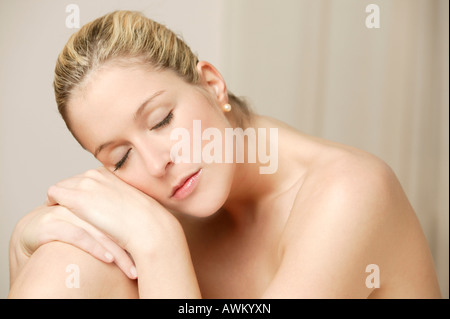 Smiling young blonde woman with closed eyes - Stock Photo