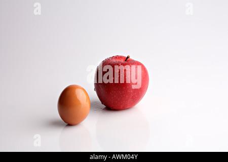 Boskoop apple beside a brown egg - Stock Photo
