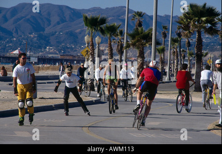 Group of people skating and cycling on boulevard Venice Los Angeles California USA - Stock Photo