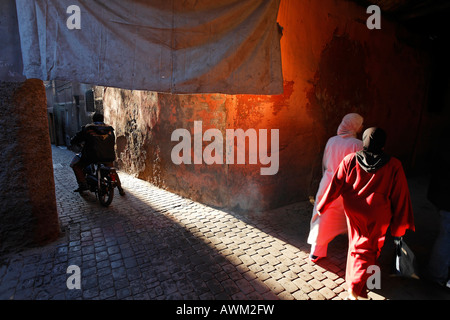 Motorcyclist driving and women walking through an alley in the historic Medina quarter of Marrakesh, Morocco, Africa - Stock Photo