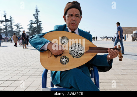 Elderly busker with guitar sitting and singing on a square, Place Moulay Hassan, Essaouira, Morocco, Africa - Stock Photo