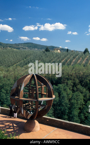 Tourists near a globe sculpture overlooking olive trees, Vinci, Tuscany, Italy - Stock Photo