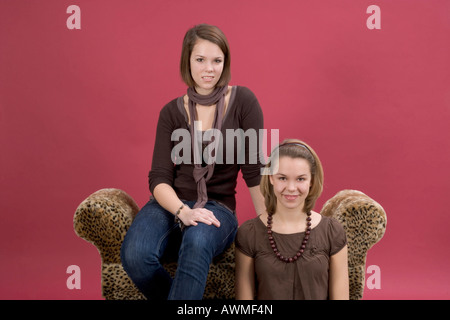 Two girls, pre-teens, early teens sitting on a tiger-print couch - Stock Photo