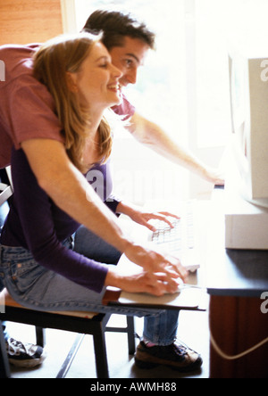 Couple looking at computer screen, man leaning over woman's shoulder, side view - Stock Photo