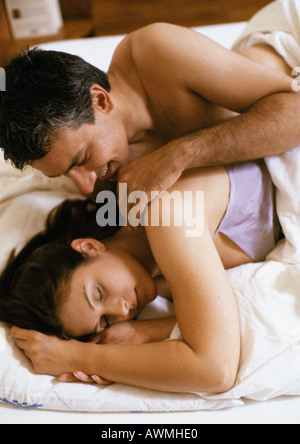 Couple lying in bed, man touching woman's shoulder - Stock Photo