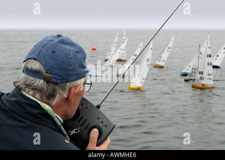 A man controls an R/C sailboat during a race. - Stock Photo