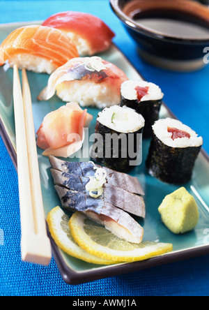 Various types of sushi on plate with chopsticks, close-up - Stock Photo