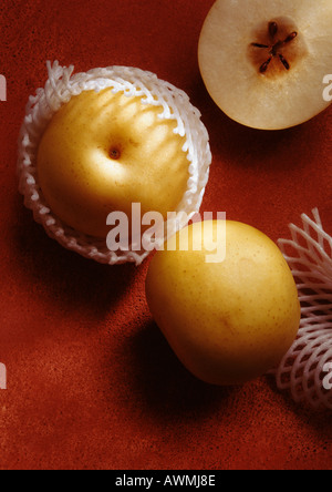 Asian pears, one in cross section, high angle view, close-up - Stock Photo