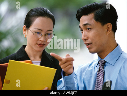 Businessman, businesswoman side by side, woman holding folders, head and shoulders - Stock Photo