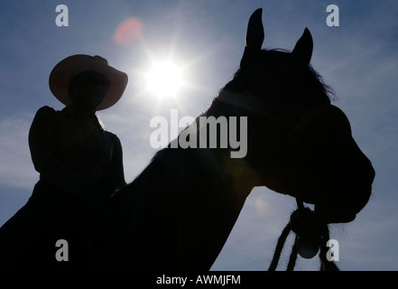 Silhouette of a horse with rider with cowboy hat in front of glaring sun - Stock Photo