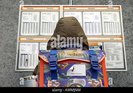 Pupil with schoolbag in front of bus timetable, Esslingen, Baden-Wuerttemberg, Germany - Stock Photo