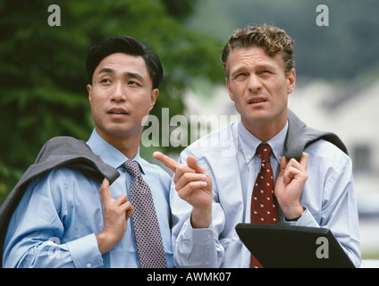 Two business associates standing outdoors having discussion, holding jackets over shoulder - Stock Photo