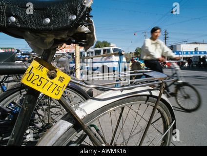 China, Beijing, close-up of old bicycle, man riding by on bicycle in background, blurred - Stock Photo