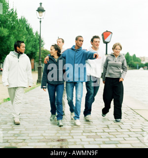 Six young people walking together on cobblestones - Stock Photo