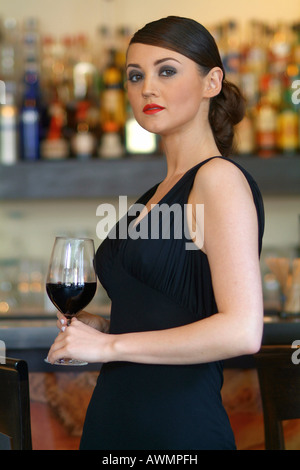 Young woman wearing a black evening dress drinking a glass of red wine at the bar - Stock Photo