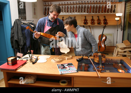 Violin-maker (luthier) with a customer in his shop - Stock Photo