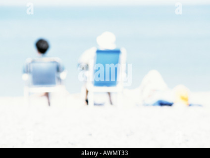 Couple sitting in chairs on the beach, rear view, blurred - Stock Photo