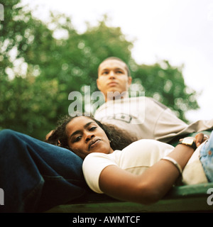 Young woman resting head on young man's lap, low angle view - Stock Photo