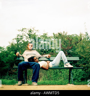 Young woman resting head on young man's lap, on bench outside. - Stock Photo