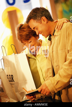Man and woman with shopping bags, paying for purchase with check, waist up - Stock Photo