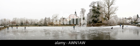 Panorama shot, kids skating on frozen lake, Hesse, Germany, Europe - Stock Photo