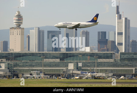 Lufthansa 737 approaching for landing with Frankfurt's skyline in the background (composing shot), Frankfurt International - Stock Photo