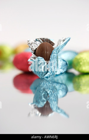 Chocolate Easter eggs laid out on a mirror, one partially unwrapped in the foreground - Stock Photo